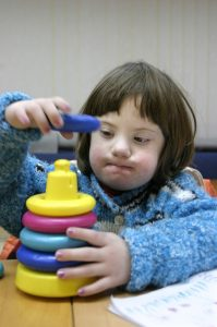 A child with Down syndrome is playing with toys
